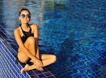 Beautiful happy female model posing by the pool, outdoor summer Stock Photo