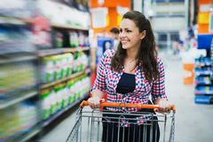 Beautiful happy female shopper in supermarket. Beautiful happy female shopper shopping in supermarket stock images