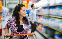 Beautiful happy female shopper in supermarket royalty free stock images