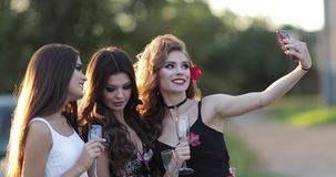 Beautiful happy friends gathering on party and doing photo. Gorgeous smiling girl drinking champagne and having fun outside. Three pretty ladies holding stock footage