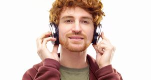 Beautiful happy fun young adult redhead man listening to music using headphones and dancing.Person action.People video stock footage