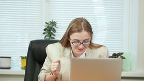 Happy funny young woman in office dancing sitting at the computer. Rejoices, fools around, having fun. Beautiful happy funny young woman in office dancing stock video