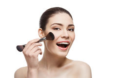 Beautiful happy girl applying blush with brush. Beautiful happy young woman applying blush with duo-side brush. Isolated over white background. Copy space Stock Photos