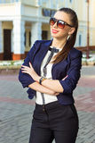 Beautiful, happy girl in business style is in the city wearing sunglasses in a jacket Stock Images