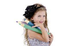 Beautiful happy girl carrying big crayons Stock Photo