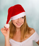 Beautiful happy girl in a Christmas hat. An attractive young girl in a red Christmas hat royalty free stock images