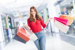 Beautiful happy girl with credit card and shopping bags in shopping mall. Shopping Center in the background. royalty free stock photos