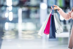 Beautiful happy girl with credit card and shopping bags in shopping mall. Shopping Center in the background. royalty free stock photo