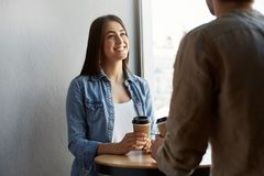 Beautiful happy girl with dark hair in white t-shirt under denim shirt , drinks coffee and smiling, listening to friend Stock Image
