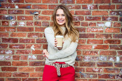 Beautiful happy girl drinking coffee and smiling near red brick wall Royalty Free Stock Photos