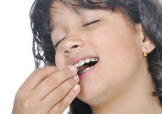Beautiful happy girl eating chocolate. On isolated background Stock Image