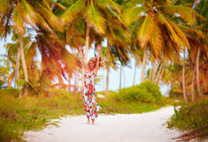 Beautiful happy girl enjoys summer vacation in tropical palm grove Stock Image