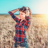 Girl in a field shirt shorts, wheat outdoor recreation, beautiful hair. A student walks after school. The woman`s long Royalty Free Stock Photos