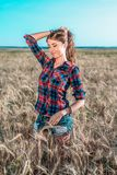 Girl in a field shirt shorts, wheat outdoor recreation, beautiful hair. A student walks after school. The woman`s long Stock Photos