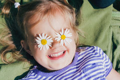 Beautiful happy girl with flowers. Beautiful happy girl with chamomile flowers on her eyes Stock Image