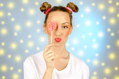 Beautiful happy girl with freckles holding and eating sweets candy lollipop with facial expression Stock Images