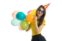 Beautiful happy girl in glasses with cone on his head holds a lot of balloons and smiling Royalty Free Stock Images