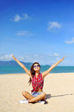Beautiful happy girl with hands raised looking to the sun behind Stock Photography