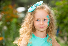 Beautiful happy girl kid with aqua make-up on birthday in park. Celebration concept and childhood, love Royalty Free Stock Photos