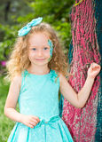 Beautiful happy girl kid with aqua make-up on birthday in park. Celebration concept and childhood, love Stock Photos