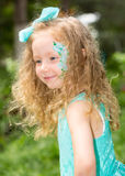 Beautiful happy girl kid with aqua make-up on birthday in park. Celebration concept and childhood, love Royalty Free Stock Photo