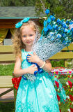 Beautiful happy girl kid with a bouquet of flowers on birthday in park. Celebration concept and childhood, love Stock Photos