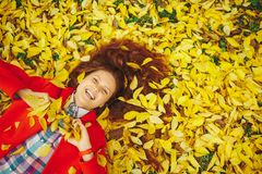 Beautiful happy girl laying in yellow autumn leaves. Stock Photography