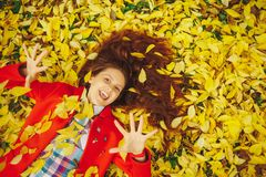 Beautiful happy girl laying in yellow autumn leaves. stock image