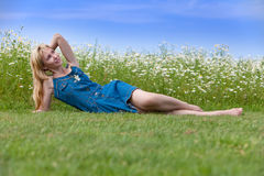 The young slender blonde in a blue sundress lies on a green grass Stock Photos