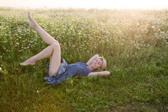 Beautiful happy girl lies in the field of chamomiles Stock Photo