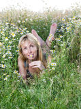 Beautiful happy girl lies in the field of chamomiles and guesses on a chamomile Royalty Free Stock Images