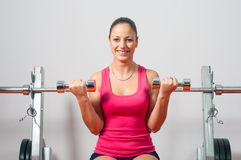Beautiful happy girl lifting dumbbells in the bodybuilding gym Stock Photography