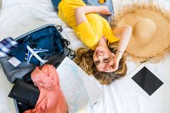 beautiful happy girl lying on bed with travel bag airplane model map royalty free stock image