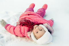 Beautiful happy girl lying on the snow Royalty Free Stock Image