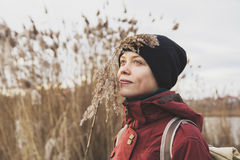 Beautiful happy girl near a lake. In nature with a cane in his hand, harmonious sensations. traveler girl enjoying life and meditates Royalty Free Stock Photos
