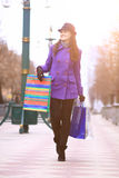 Beautiful happy girl with purchases walking down the street. Royalty Free Stock Photography