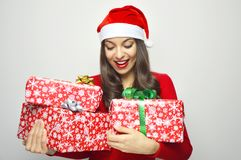 Beautiful happy girl with Santa Claus hat looks her christmas gifts on gray background Stock Photos