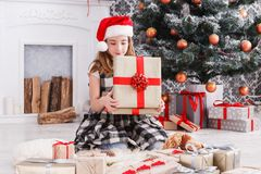 Beautiful girl in santa hat unwrapping christmas presents Stock Images