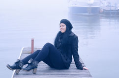 Beautiful happy girl sitting on river dock on misty autumn day Stock Images