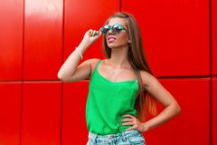 Beautiful happy girl in a stylish sunglasses near a modern stock photo
