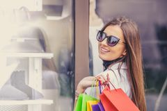 Beautiful happy girl in sun glasses is holding shopping bags stock photos