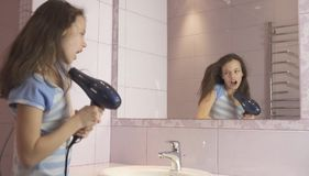 Beautiful happy girl teenager dries hair with hair dryer and sings and dances in front of a mirror in the bathroom. Beautiful happy girl teenager dries hair with stock photography