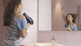 Beautiful happy girl teenager dries hair with hair dryer and sings and dances in front of a mirror in the bathroom. Beautiful happy girl teenager dries hair with Stock Photo