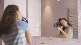 Beautiful happy girl teenager dries hair with hair dryer and sings and dances in front of a mirror in the bathroom. Beautiful happy girl teenager dries hair with Royalty Free Stock Images