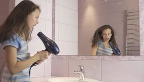 Beautiful happy girl teenager dries hair with hair dryer and sings and dances in front of a mirror in the bathroom. Beautiful happy girl teenager dries hair with Stock Photos