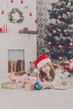Beautiful girl in santa hat unwrapping christmas presents. Beautiful happy girl unwrap christmas present box on holiday morning in beautiful room interior Royalty Free Stock Photo