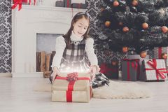 Beautiful girl unwrapping christmas presents. Beautiful happy girl unwrap christmas present box on holiday morning in beautiful room interior. Female child open Royalty Free Stock Photo