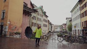Beautiful happy girl walking on the bridge near the old buildings, playing with her black umbrella. Rainy day. Brunette. Young woman wearing yellow coat and stock video
