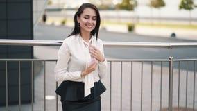 Beautiful happy girl in white blouse, black skirt posing on camera, slow motion. Beautiful smiling girl in white blouse, black skirt posing on camera near stock video