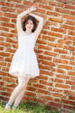 Beautiful happy girl in white dress standing at a brick wall Royalty Free Stock Photo